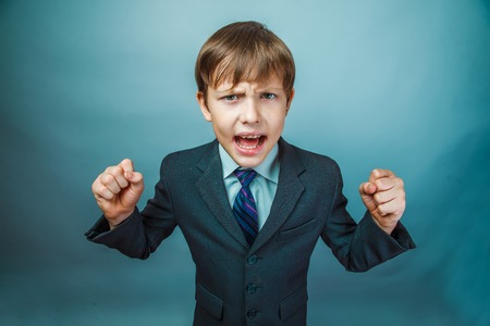 teen boy: Teen boy businessman in a suit swearing angry shouts on a blue background photo studio