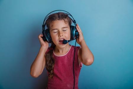 adorable child: Teen girl singing in a microphone and listening to music with headphones on a blue background photo studio
