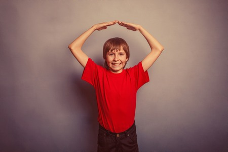 suo: Boy, teenager, twelve years in the red t-shirt, made his hands above his head house retro