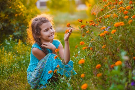 explores: teen girl sitting on his haunches and touching orange flower in nature studies explores the outside in the summer Photo