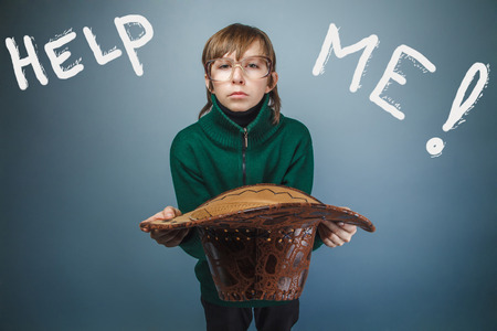 help me: Teen boy homeless asking for help holding a hat inscription help me