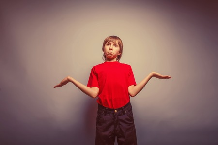 ignorance: boy teenager European appearance in a red shirt spread his arms on a gray background, the ignorance retro