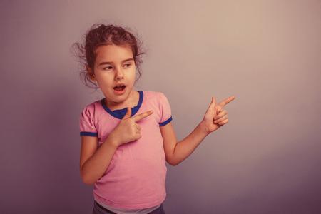 alzando la mano: niña de europeos apariencia de 6 años muestra un lado, la boca abierta en un fondo gris retro Foto de archivo