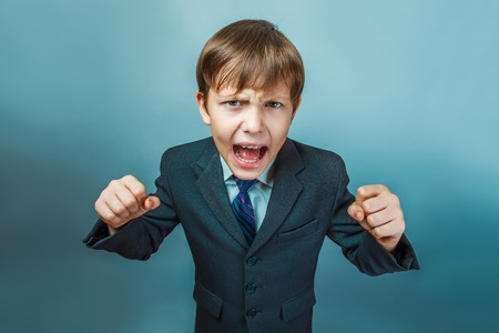screaming: a boy of twelve European appearance in a suit shouting angry  on a gray  background