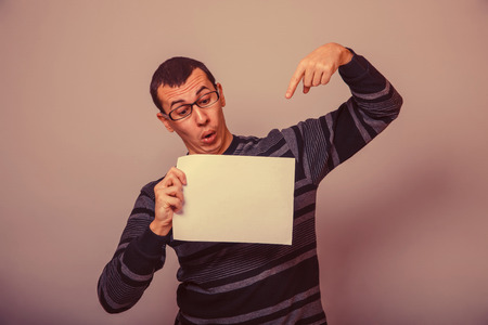 30 years: European-looking man of 30  years holding a blank sheet retro Stock Photo