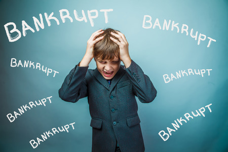 fails: Teen boy businessman fails bankrupt holding his head inscription studio background