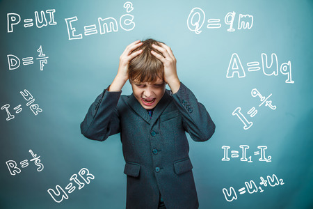 fails: Teen boy scientist fails holding his head formula physics science studio background experiencing problems
