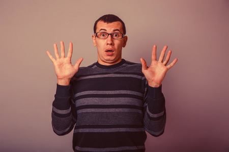 European-looking male of about thirty raised his hands palms outward surprised on a gray background retro Stock Photo