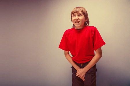 incontinence: Boy, teenager, twelve years in the red shirt wants to use  toilet, cystitis retro