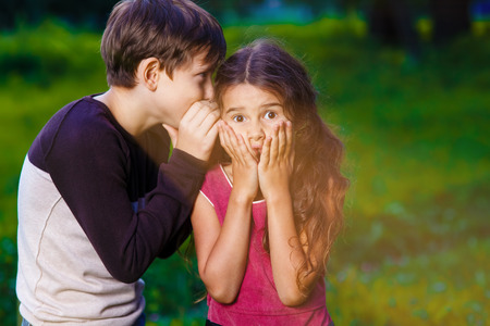 secret: girl whispering in the ear of the boy tells the secret hearings in nature photos sunlight