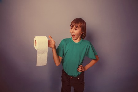 European-looking  boy of ten  years with  toilet paper on a gray background retro