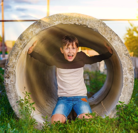 young fear: Teen boy shouts in a tube claustrophobia agoraphobia mental illness sunlight