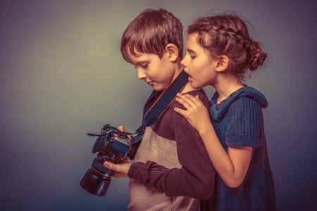 beautiful boys: Teenage boy with a girl watching pictures on the camera on a  gray  background retro Stock Photo