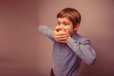 boca cerrada: muchacho adolescente de 10 años de aspecto europeo cerró la boca con sus manos sobre un fondo gris retro