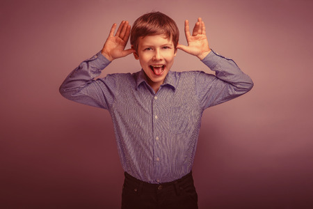 grimaces: teenager boy brown hair of European appearance grimaces experiencing joy on a gray background retro Stock Photo