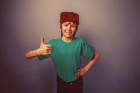 skullcap: Muslim boy of ten years, skullcap, thumbs up on a gray background retro