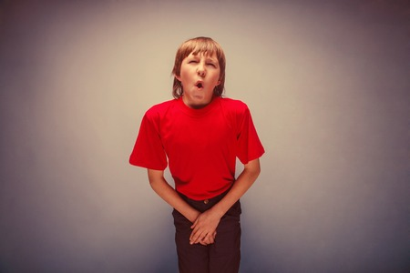 incontinence: Boy, teenager, twelve years in the red shirt wants to use the toilet, cystitis retro Stock Photo