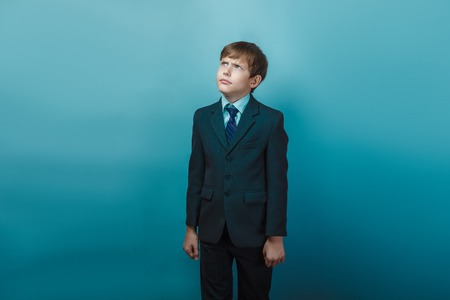 frowns: a boy of twelve European appearance in a suit looking up frowns on a gray background Stock Photo