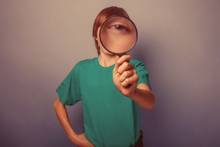 keen: European-looking boy of ten years is looking through a magnifying glass, a keen eye on gray background retro