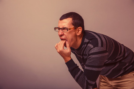 male of European appearance causes vomiting putting his fingers in his mouth on a gray background, nausea retro