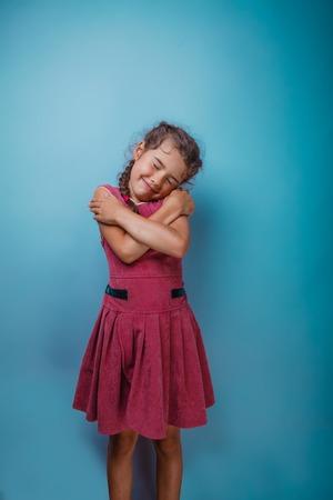 Girl seven years old, European-looking brunette in a pink dress hugging herself shoulders closed her eyes on gray background, smiling, sleeping