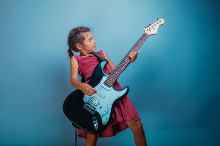 seven years: Girl seven years old, European-looking brunette in a pink dress playing guitar t closed her eyes on gray background, music Stock Photo