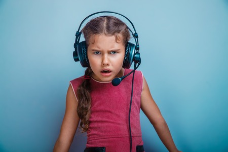 frowned: Teen girl child seven years, European appearance brunette in a pink dress in big headphones frowned on  gray background, confusion, anger