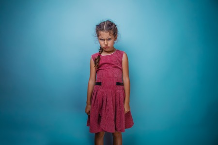 mood: Girl seven years old, European-looking brunette in a pink dress her head and frowned on gray background, bad mood, anger Stock Photo