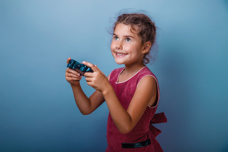 seven years: Girl seven years old, European-looking brunette in a pink dress holding a joystick and smiling on gray background, happiness, joy, game Stock Photo