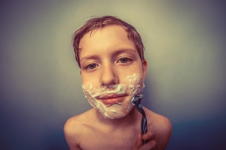decade: the boy of the European appearance decade person shaves, shaving foam on a  gray  background retro