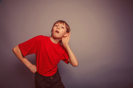 decade: European appearance boy overhears a decade, interest, ear on gray background retro Stock Photo