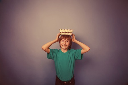 ten empty: European -looking  boy of ten years holding an empty basket in hand on gray background retro Stock Photo