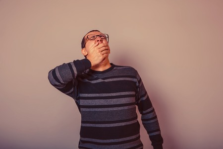 drowsiness: male European appearance brunet in sweater yawns covers her mouth on a gray background, drowsiness retro