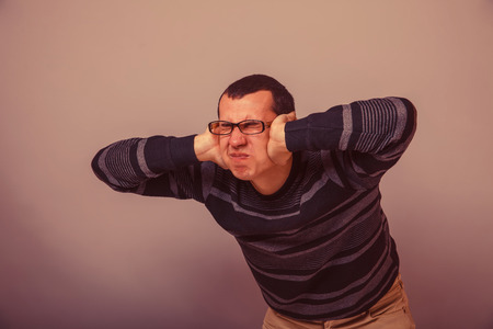 hands covering ears: European-looking male covering his ears with his hands brunet on a gray background retro