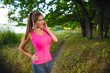 fitness woman: woman running in green forest listening to music with headphones healthy lifestyle sports athlete runner Life style