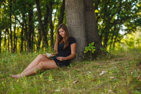 woman girl sits reading a book under a tree in the forest park on the nature of summer in a black dress blond Life style Stock Photo
