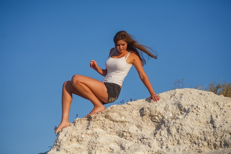 acrophobia: woman blonde woman descends from the high mountains boitsya phobia disease acrophobia fear of heights Stock Photo