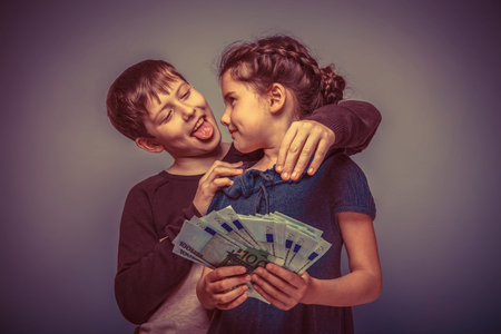 to tease: teen girl about seven years old holding a money boy teen hugging her shows tongue on a gray background, notes, fun, tease retro
