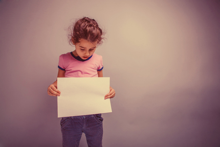 blank slate: girl child 6 years of European appearance holds a blank slate, looking down on a gray background retro