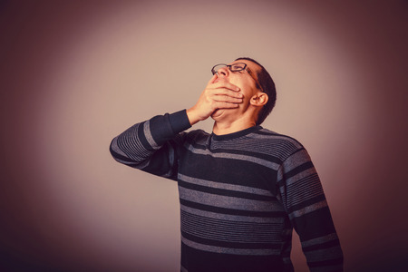 tedious: male of European appearance brunet covered his mouth with his hand and yawning, drowsiness cross process retro