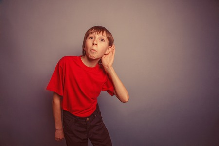 eavesdropping: Boy, teenager, twelve years old, in a red shirt, holding a hand behind his ear, eavesdropping retro Stock Photo