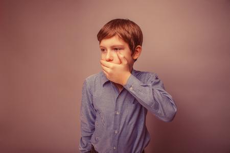 boca cerrada: Muchacho adolescente aspecto europeo mano cabello castaño boca cerrada siente miedo retro