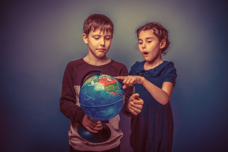 seven years: Teen boy and girl of European appearance seven years are holding a globe on his finger show a gray background, travel, emotions retro