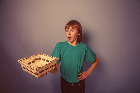 ten empty: European-looking  boy of  ten years  holding an empty basket in hand on gray background retro