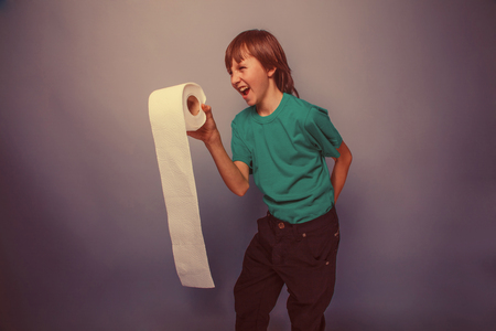 papel de baño: Europea de futuro niño de diez años con el papel higiénico, quiere usar el baño en un fondo gris retro Foto de archivo