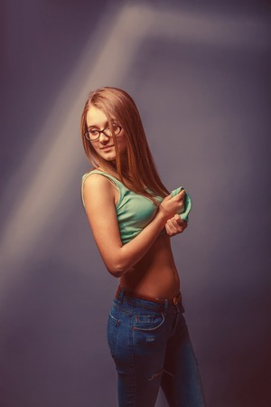 bared: European-looking girl of twenty years in glasses bared stomach on a gray background retro