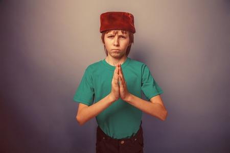 skullcap: Muslim boy of ten  years, skullcap, prayer on a gray background retro Stock Photo