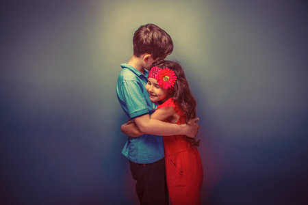 cute young boy: teen girl hugging a teenage  boy on a gray  background retro