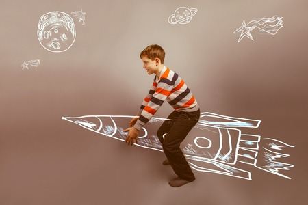 invisible object: European-looking boy of ten years raises an invisible object on gray background retro Stock Photo