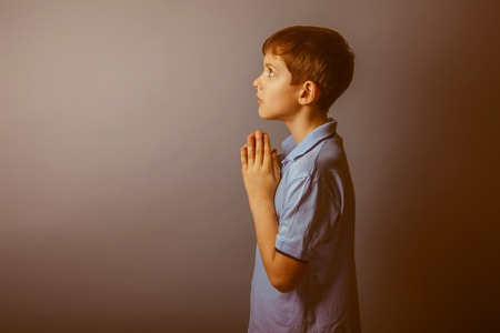 christian youth: boy teenager European appearance in a blue shirt brown praying laid his head on a gray background, faith retro Stock Photo
